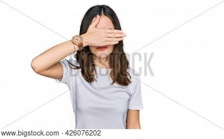 Young beautiful woman wearing casual white t shirt covering eyes with hand, looking serious and sad. sightless, hiding and rejection concept
