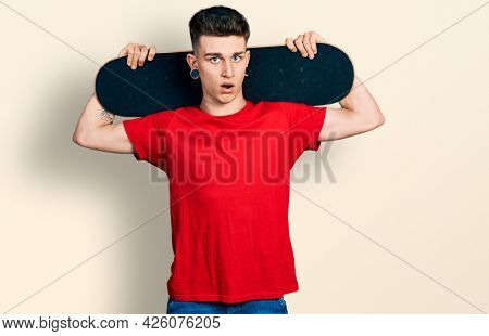 Young caucasian boy with ears dilation holding skate over shoulders in shock face, looking skeptical and sarcastic, surprised with open mouth