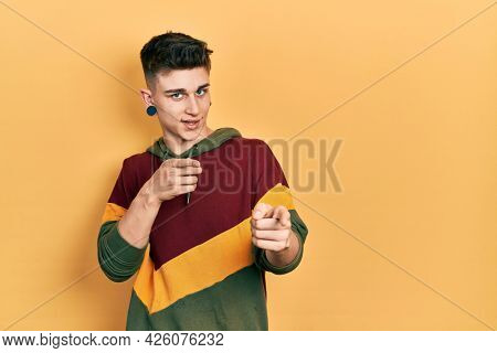 Young caucasian boy with ears dilation wearing casual sweatshirt pointing fingers to camera with happy and funny face. good energy and vibes.