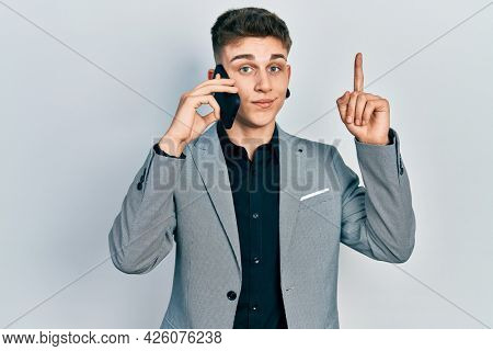 Young caucasian boy with ears dilation having conversation talking on the smartphone smiling with an idea or question pointing finger with happy face, number one