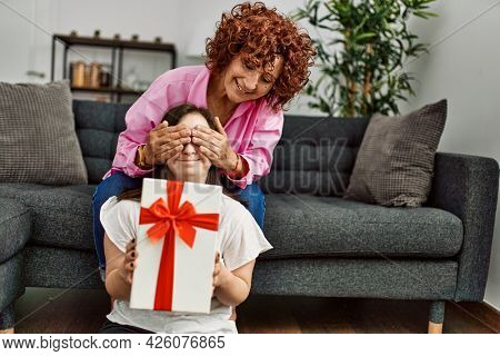 Mature mother and down syndrome daughter at home giving a surprise gift to the other
