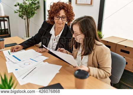 Group of two women working at the office. Mature woman and down syndrome girl working at inclusive teamwork.