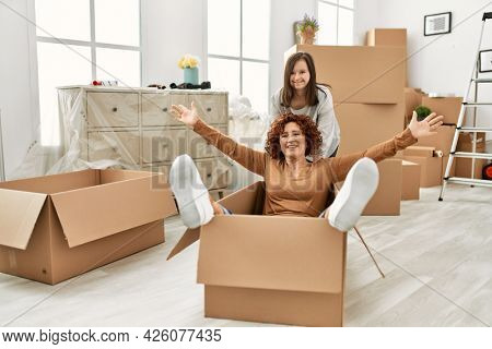Mature mother and down syndrome daughter moving to a new home, having fun inside box