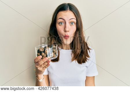 Young brunette woman holding raw hazelnuts scared and amazed with open mouth for surprise, disbelief face