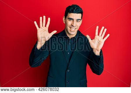 Handsome hispanic man wearing business clothes showing and pointing up with fingers number ten while smiling confident and happy.