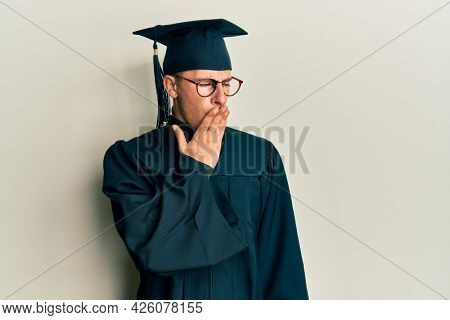 Young caucasian man wearing graduation cap and ceremony robe bored yawning tired covering mouth with hand. restless and sleepiness.
