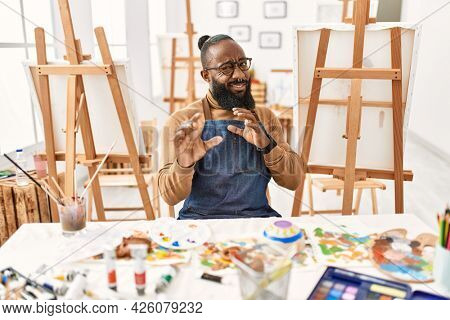 African american artist man at art studio disgusted expression, displeased and fearful doing disgust face because aversion reaction. with hands raised