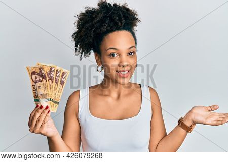 Young african american girl holding 5000 hungarian forint banknotes celebrating achievement with happy smile and winner expression with raised hand