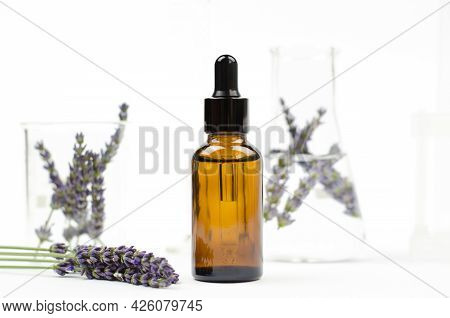 Lavender Essential Oil In A Brown Bottle With A Dropper. Natural Essential Oil And Lavender Flowers
