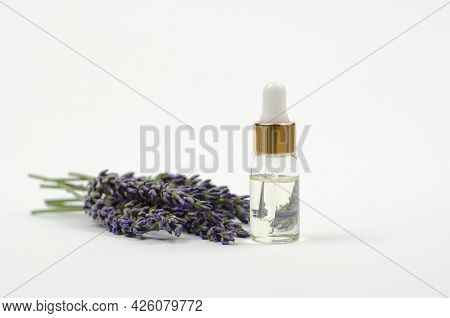 Natural Essential Oil And Lavender Flowers On A White Background. Lavender Essential Oil In A Transp