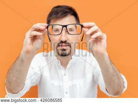 Portrait Of Thoughtful Caucasian Man Holding Eye Glasses Outstretched And Looking Through It While S