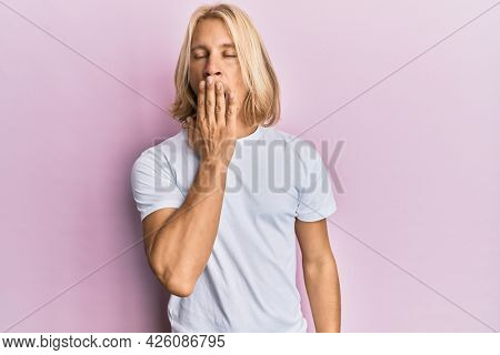 Caucasian young man with long hair wearing casual white t shirt bored yawning tired covering mouth with hand. restless and sleepiness.