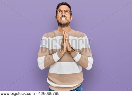 Handsome man with beard wearing casual clothes and glasses begging and praying with hands together with hope expression on face very emotional and worried. begging.