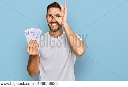 Handsome man with beard holding 20 swedish krona banknotes smiling happy doing ok sign with hand on eye looking through fingers