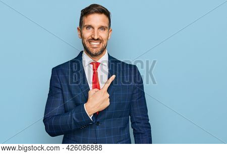 Handsome man with beard wearing business suit and tie cheerful with a smile of face pointing with hand and finger up to the side with happy and natural expression on face