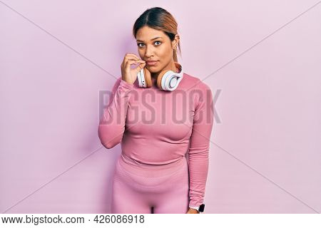 Beautiful hispanic woman wearing gym clothes and using headphones mouth and lips shut as zip with fingers. secret and silent, taboo talking
