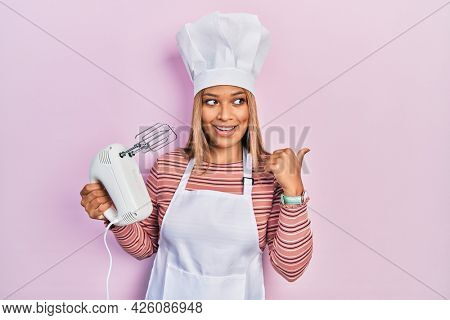 Beautiful hispanic woman holding pastry blender electric mixer smiling with happy face looking and pointing to the side with thumb up.