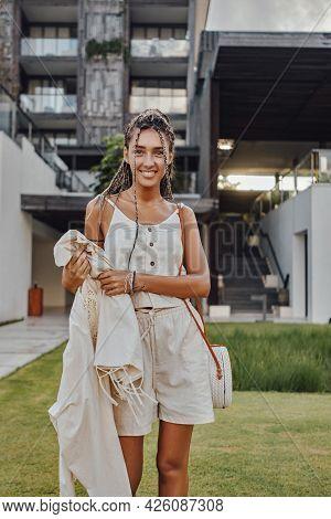 Joyful Woman Standing On Lawn Against Mansion