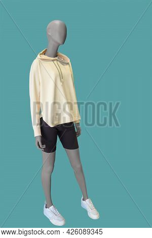 Full Length Image Of A Female Display Mannequin Wearing Yellow Hooded Sweatshirt And Black Shorts Is