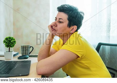 Short-haired, Gray-haired Brunette Woman Rests Her Head On Her Hand While Sitting At A Table In Fron