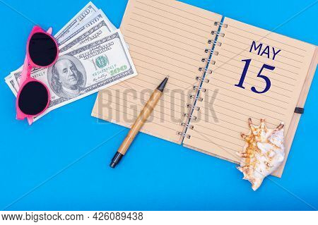 15th Day Of May. Travel Concept Flat Lay - Notepad With The Date Of 15 May Pen, Glasses, Dollars And