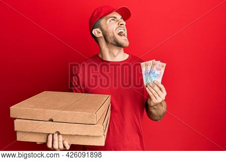 Young caucasian man holding delivery box and swiss franc banknotes angry and mad screaming frustrated and furious, shouting with anger looking up.