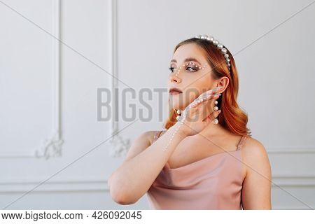 Profile Portrait Of A Woman With Pearl Makeup On Her Face And Hand, With Pearl Accessories In A High