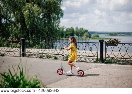 Lifestyle Portrait A Six-year-old Girl In A Yellow Dress Rides A Scooter Along The River On A Sunny