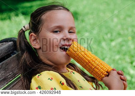 A Happy Five-year-old Girl Nibbles Corn Sitting On A Bench In The Park On A Summer Day. Delicious Bo