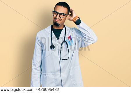 Young african american man wearing doctor uniform and stethoscope confuse and wondering about question. uncertain with doubt, thinking with hand on head. pensive concept.