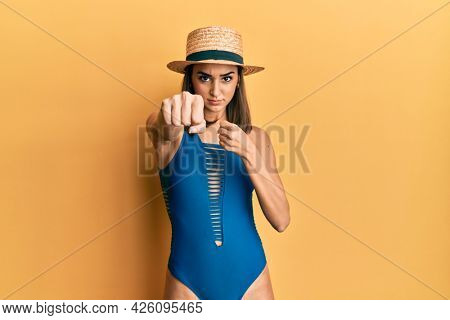 Young brunette girl wearing swimsuit and summer hat punching fist to fight, aggressive and angry attack, threat and violence