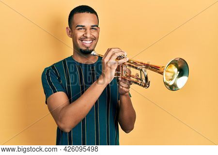 Young african american man playing trumpet celebrating crazy and amazed for success with open eyes screaming excited.