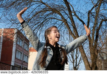 Pretty Blonde Girl In Denim Clothes On The Background Of A Blue Sky Expresses Joy And Delight, Admir