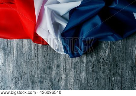 high angle view of a flag of france on a gray rustic wooden background with some blank space on the bottom