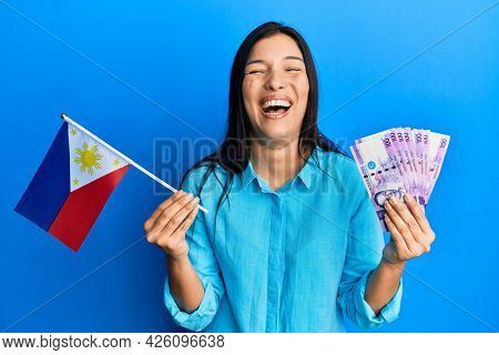 Young latin woman holding philippines flag and pesos banknotes smiling and laughing hard out loud because funny crazy joke.