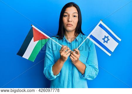 Young latin woman holding palestine and israel flags relaxed with serious expression on face. simple and natural looking at the camera.