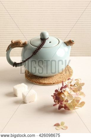 Porcelain Teapot With Sugar On A White Table