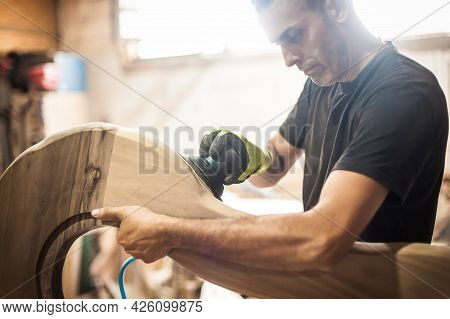 Craftsman Using Electric Sander, To Smoothen The Wood Texture