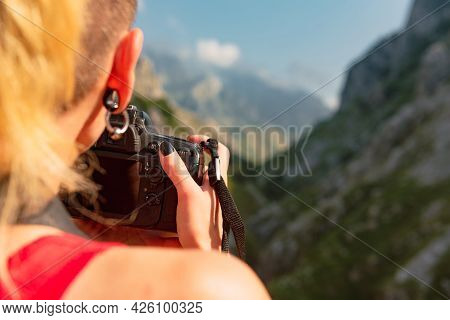 Unknown Person Holding A Camera And Taking Pictures Of A Mountain Passage. Hiker Taking Photos