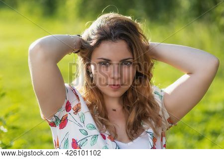 Atractive Beautiful  Young Woman With Both Hands In Her Hair Is Posing Outdoors. Horizontally.
