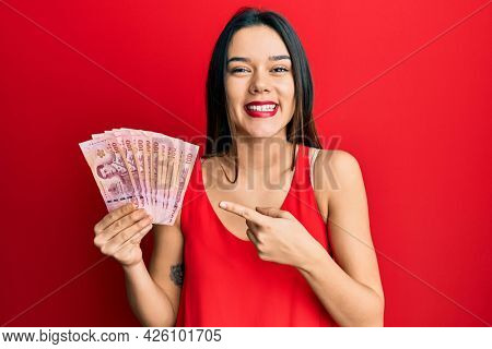 Young hispanic girl holding thai baht banknotes smiling happy pointing with hand and finger