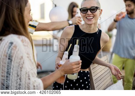 Young Group Of Stylish People Having Fun At Party Outdoors, Two Female Friends Drinking Cold Drinks