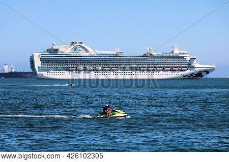 July 6, 2021 In Long Beach, Ca:  Person Jet Skiing On The Bay Besides Anchored Cruise And Freighter