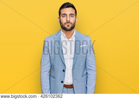 Young hispanic man wearing business jacket with serious expression on face. simple and natural looking at the camera.