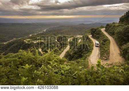 Sinuous Mountain Dirt Road With A Sunset Sky And A Truck Driving In It. Tucumán Province, Argentina