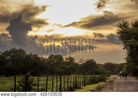 Three Riders In A Dirt Road With A Very Expressive Sky In Córdoba, Argentina  Three Riders And Three