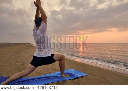 Man Stands On Blue Exercise Man Doing Virabhadrasana One Pose. Man Practices Warrior One Asana At Se