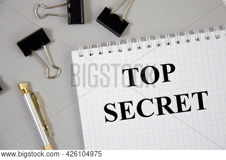 Top Secret Word Written On Gray Background With Pencils And Paper Clips