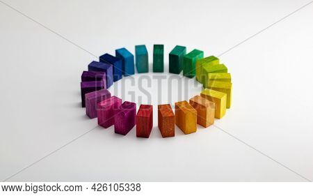 Colors in unity. Circle of colored blocks representing unity of diverse elements (colors).  Wooden blocks placed in a a circle on a neutral white background, with natural shadows.