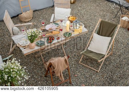 Beautifully Served Wooden Table In Natural Boho Style Outdoors. Dining Table Decorated With Field Fl